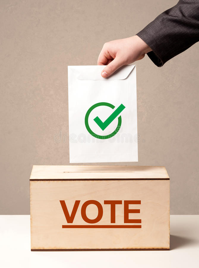 Закройте вверх мужской руки кладя голосование в урну для избирательных бюллетеней стоковая фотография