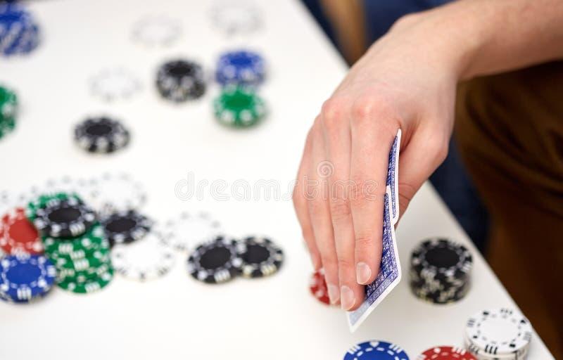 Закройте вверх мужской руки с играя карточками и обломоками стоковое изображение rf
