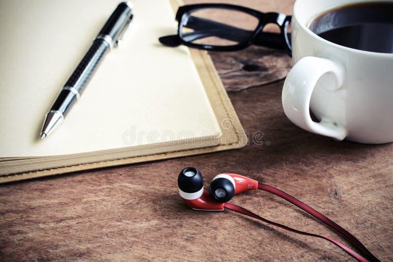 Закройте вверх наушника с кофе и тетрадью на старое деревянном стоковая фотография