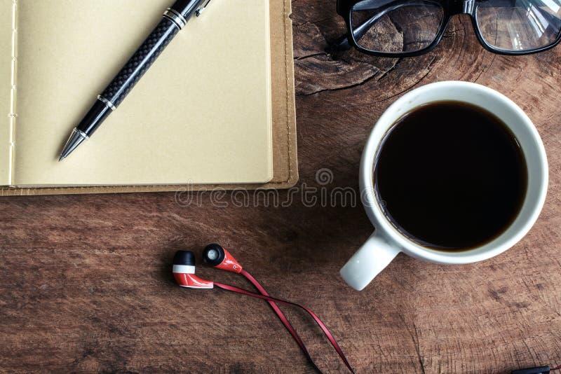 Закройте вверх наушника с кофе и тетрадью на старом деревянном tabl стоковая фотография
