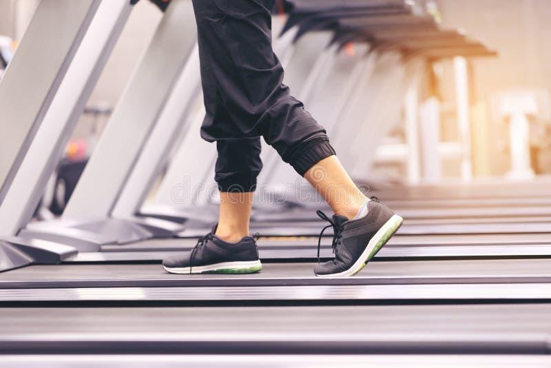 Закройте вверх на ботинке, тренировке женщины с ногами бежать на третбане и сгорите сало в теле в спортзале, здоровом образе жизн стоковые фото