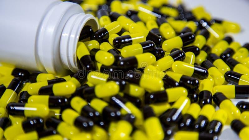 Закройте вверх на бутылке отпускаемых по рецепту лекарств падая вне Черные и желтые таблетки стоковое изображение rf