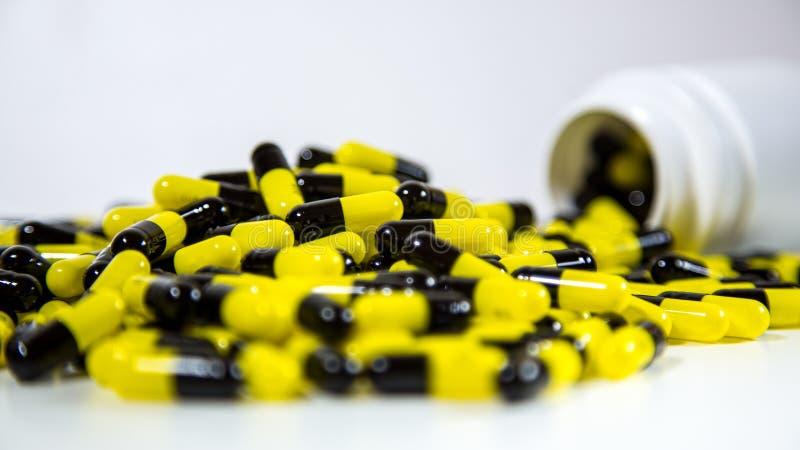 Закройте вверх на бутылке отпускаемых по рецепту лекарств падая вне Черные и желтые таблетки стоковая фотография rf