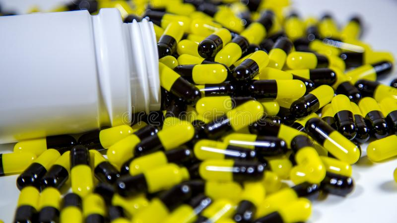 Закройте вверх на бутылке отпускаемых по рецепту лекарств падая вне Черные и желтые таблетки стоковое фото