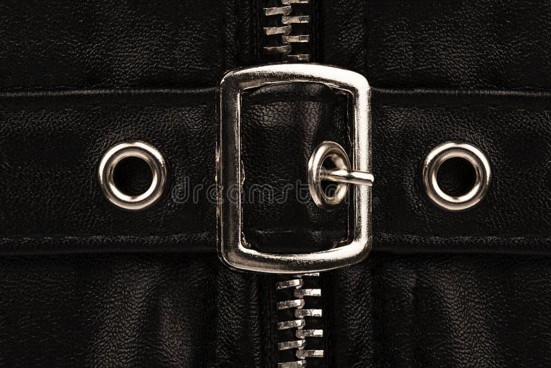 Закройте вверх на декоративной пряжке пояса на части черных кожаных одежд стоковое фото