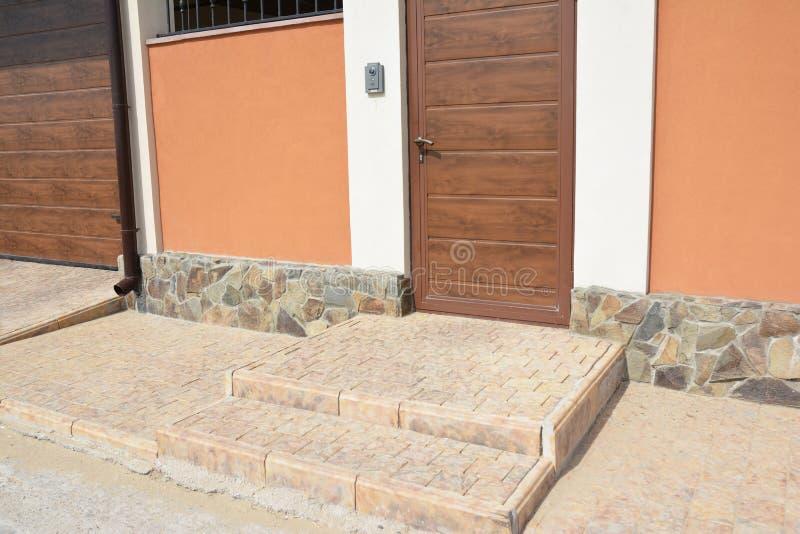 Закройте вверх на каменных шагах с дверным звоноком двери загородки входа, камерой слежения, дверью гаража и путем Умный домашний стоковые фотографии rf