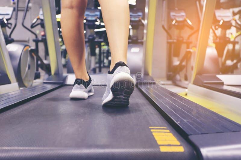 Закройте вверх на ногах ботинка, женщины фитнеса бежать на третбане и бушеле стоковое изображение