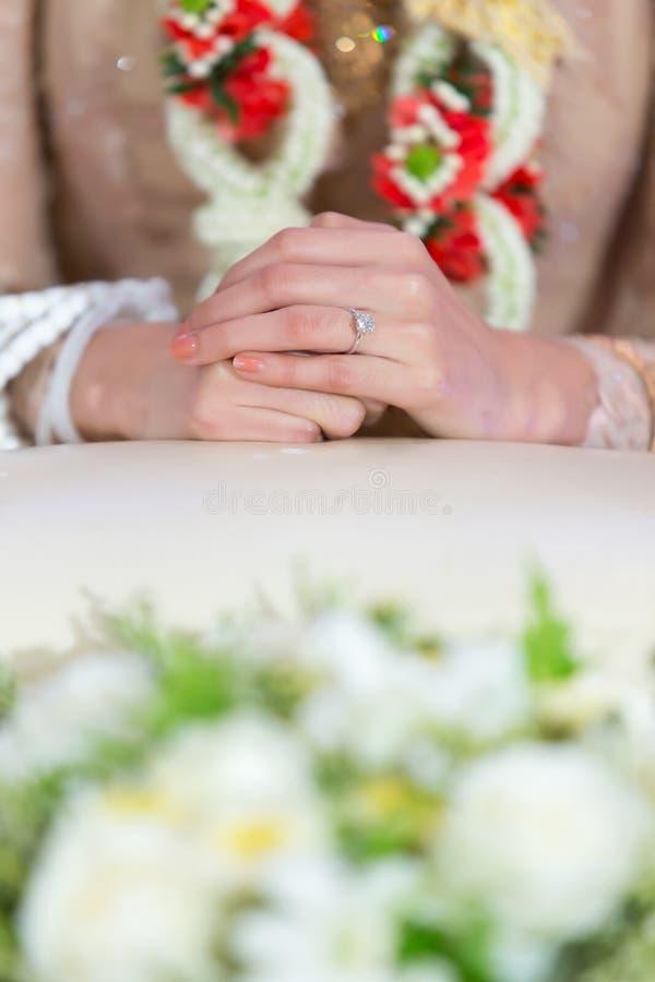 Закройте вверх на руке ` s невесты с кольцом в тайской свадьбе традиционной стоковая фотография rf
