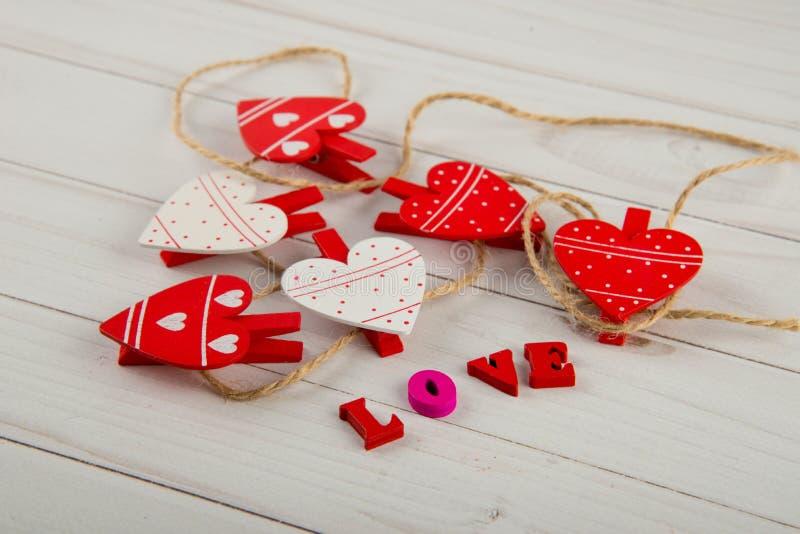 Закройте вверх на славных деревянных зажимках для белья в форме сердец в веревочке кладя на белую таблицу около слова ЛЮБОВ напис стоковые фотографии rf