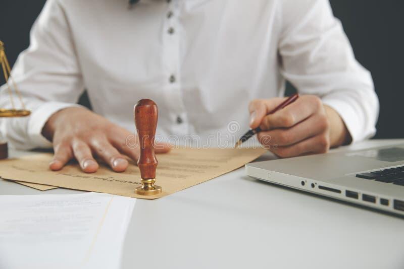 Закройте вверх на чернилах руки государственного нотариуса человека штемпелюя документ Государственный нотариус стоковые фото