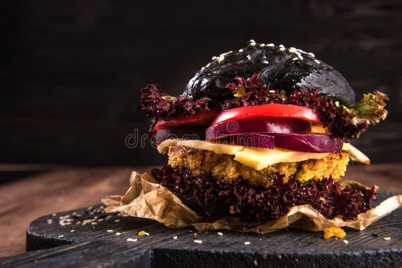 Закройте вверх на черном бургере заполненном с зажаренными луками, кусками томата и салатом стоковые изображения rf