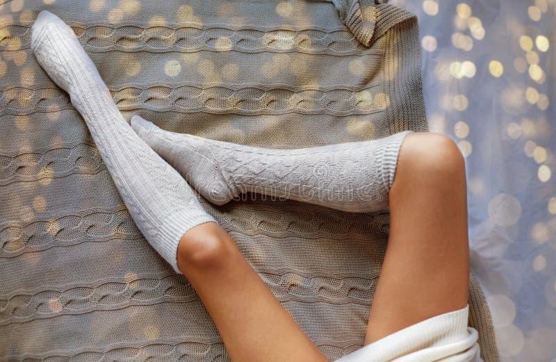 Закройте вверх ног женщины в носках колена зимы в кровати стоковые фотографии rf
