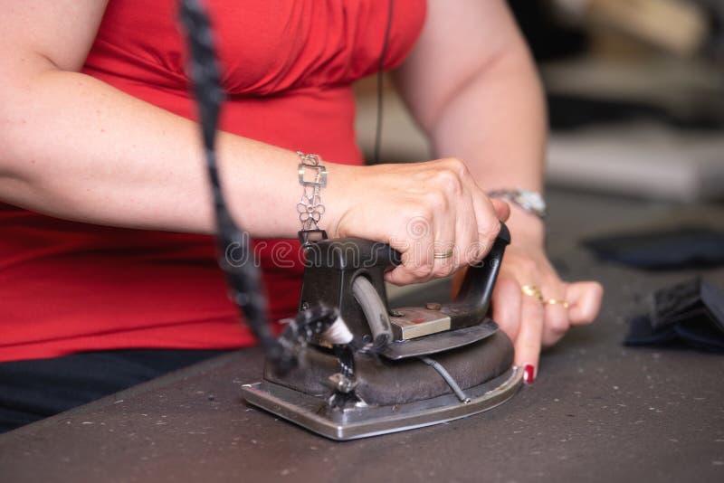 Закройте вверх одежд непознаваемого портноя утюжа со старомодным утюгом металла в традиционной студии atelier стоковые фото