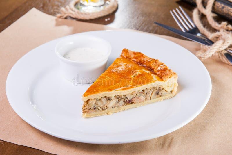 Закройте вверх одиночного куска пирога цыпленка и гриба с соусом на белой плите на таблице служат рестораном, который Селективное стоковые фото
