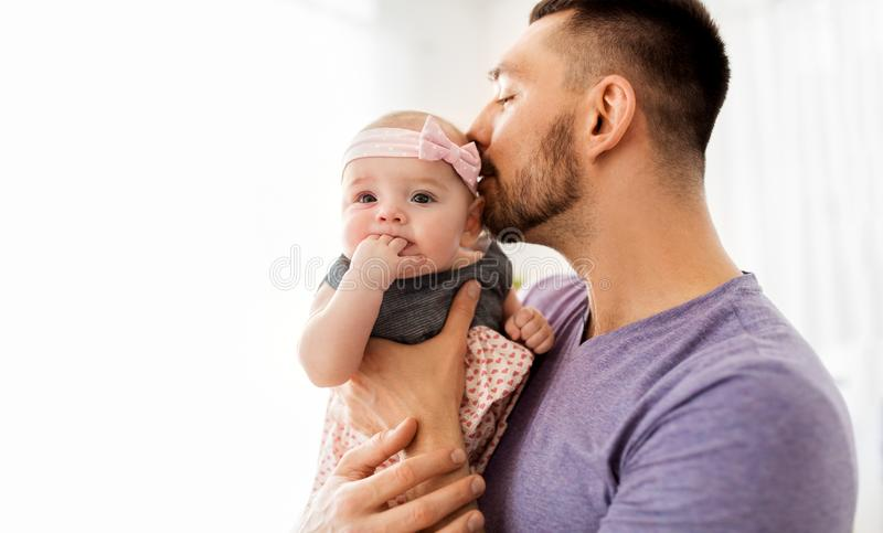 Закройте вверх отца целуя маленькую дочь младенца стоковое изображение