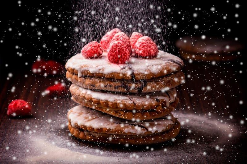 Закройте вверх очень вкусного торта с полениками на деревянном столе, против черной предпосылки, со снегом как разбросанный сахар стоковые изображения