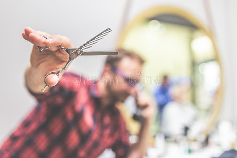 Закройте вверх парикмахера держа ножницы и звоня с ретро винтажным телефоном Концепция Scheduling стоковое изображение rf