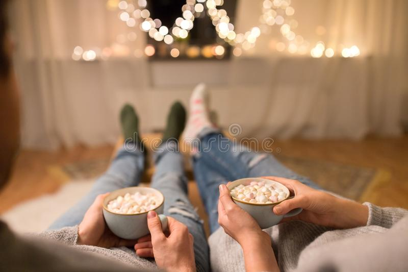 Закройте вверх пар выпивая горячий шоколад дома стоковые фото