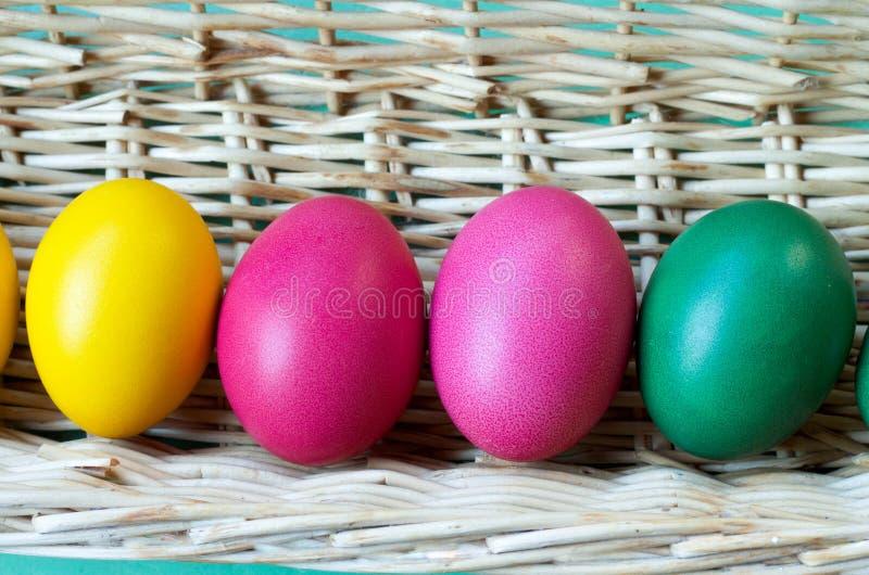 Закройте вверх 4 пасхальных яя покрашенных в корзине стоковые изображения rf