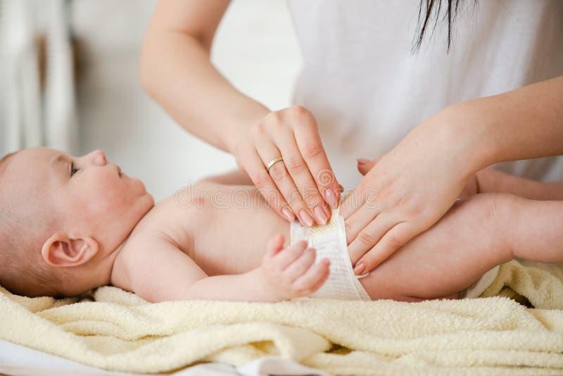 Закройте вверх пеленки починки рук на талии младенца стоковые фотографии rf