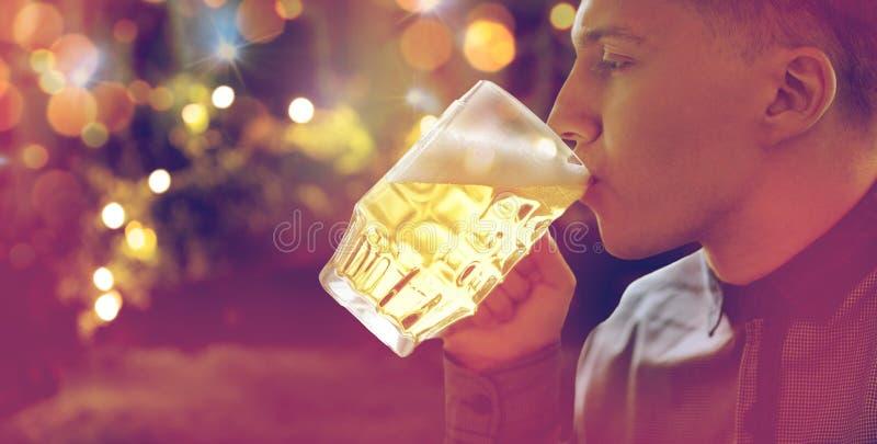 Закройте вверх пива молодого человека выпивая от стеклянной кружки стоковое изображение rf