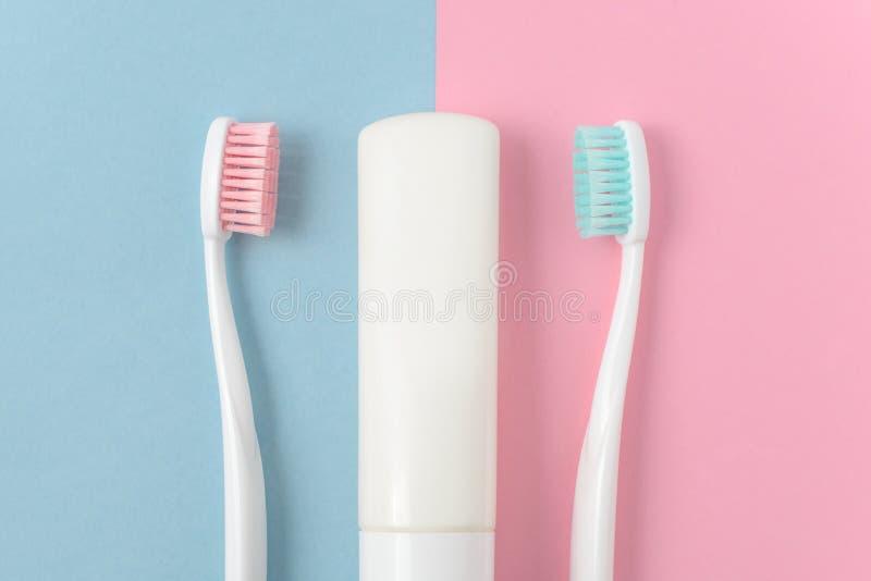 Закройте вверх 2 пластичных белых зубных щеток с пинком и голубой щетинкой и зубной пасты на розовой и голубой предпосылке стоковые фотографии rf