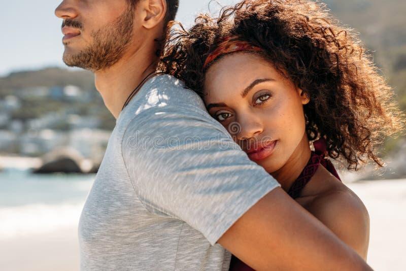 Закройте вверх положения женщины за человеком обнимая его стоковое фото rf