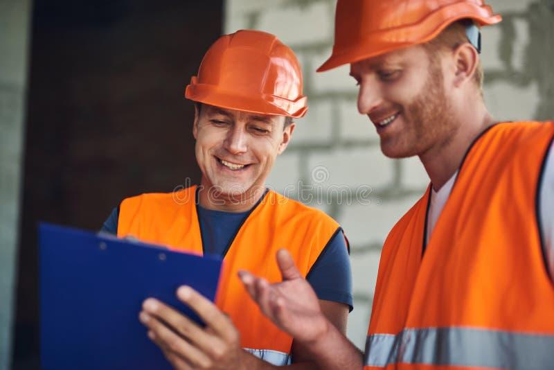 Закройте вверх положительных построителей смотря примечания и усмехаться стоковые фото