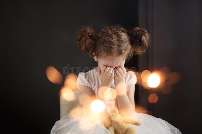 Закройте вверх портрета прелестной маленькой курчавой девушки плача Грустный день рождения, закрывал глаза Искра на прифронтовом  стоковые изображения