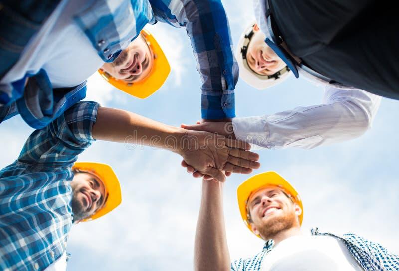 Закройте вверх построителей в защитных шлемах с руками на верхней части стоковые изображения
