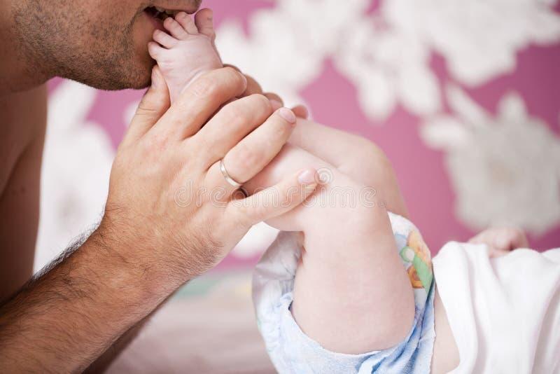 Закройте вверх, поцелуи отца его newborn пятки сына дома стоковое фото