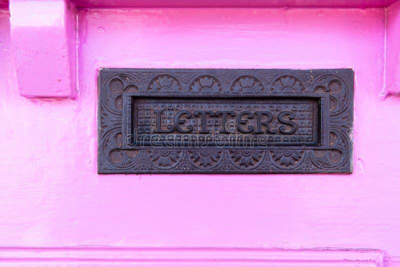 Закройте вверх почтового ящика в грубо покрашенной деревенской розовой двери стоковое изображение rf