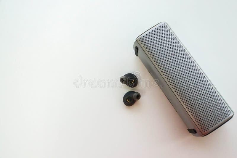 Закройте вверх по беспроволочному портативному диктору с наушниками для соединения для того чтобы слушать музыка стоковое изображение