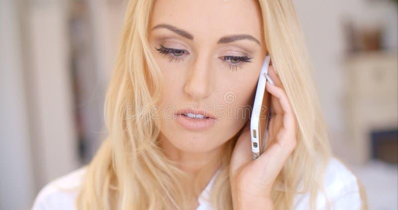 Закройте вверх по белокурой женщине вызывая через телефон стоковое фото rf