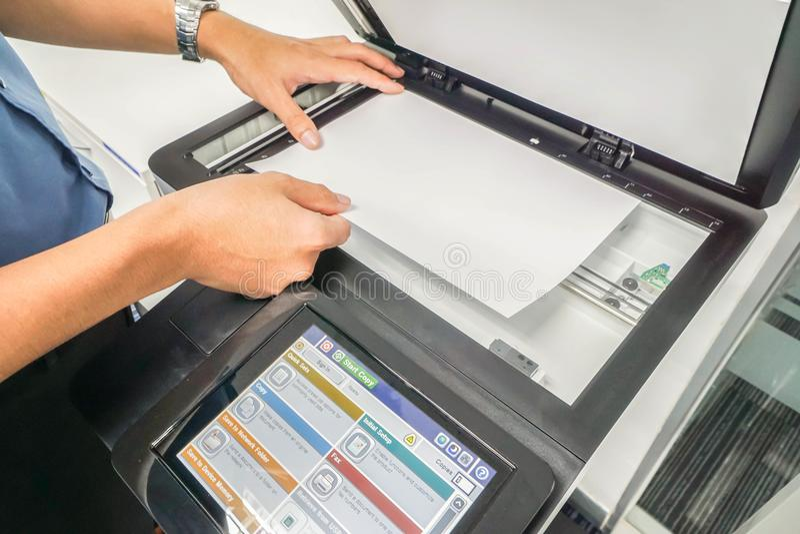 Закройте вверх по бизнесмену в голубом листе бумаги места руки рубашки на принтере стоковое фото