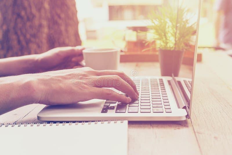 Закройте вверх по бизнесмену руки держа кофе чашки и используя компьтер-книжку i стоковые изображения rf