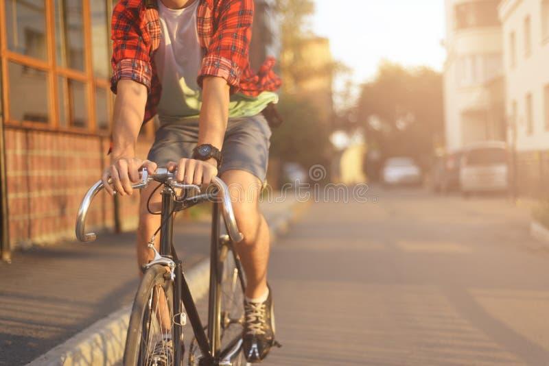 Закройте вверх по битнику на велосипеде в городе на заходе солнца стоковое фото