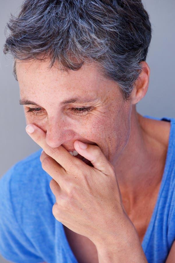 Закройте вверх по более старой женщине смеясь над с ртом заволакивания руки стоковые изображения rf