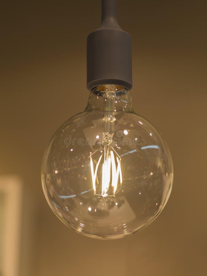 Закройте вверх по большой ретро электрической лампочке освещения на blured предпосылке стоковое изображение rf