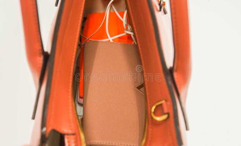 Закройте вверх по бумажнику женщины в обнажённом цвете и аксессуарам в личной кожаной сумке стоковая фотография rf