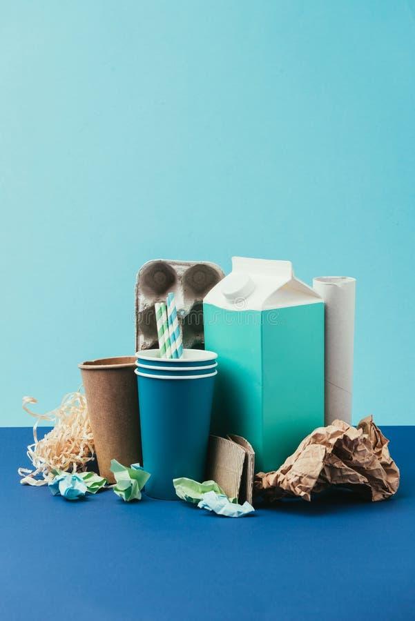закройте вверх по взгляду аранжированного картона и заверните устранимый отброс в бумагу на голубой предпосылке стоковая фотография rf