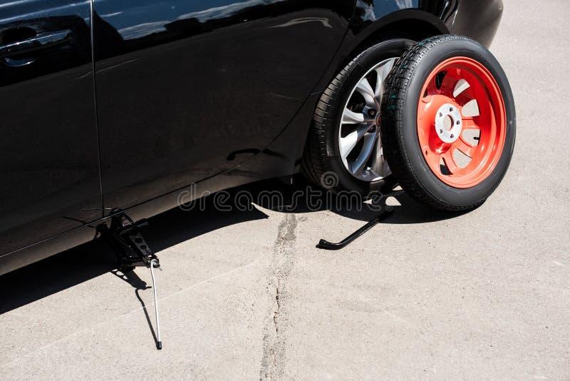 закройте вверх по взгляду винта jack, гаечного ключа колеса и утомляйте около сломленного автомобиля стоковые изображения