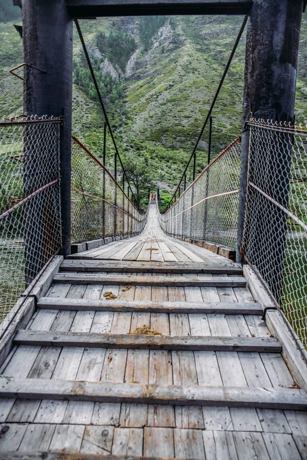 Закройте вверх по взгляду деревянного моста и туристов в горах Гималаев, стоковая фотография rf