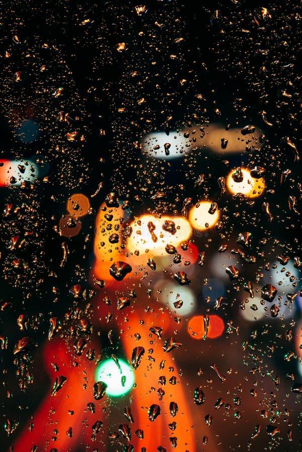 Закройте вверх по взгляду дождевых капель на светах города окна и bokeh стоковое фото rf