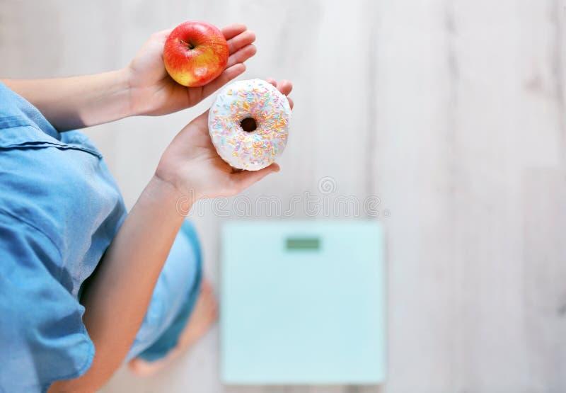 Закройте вверх по взгляду женщины делая выбор между яблоком стоковые фотографии rf