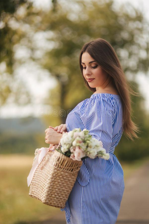 Закройте вверх по взгляду красивой беременной женщины в поле держа букет и усмехнитесь природа ослабляет стоковое изображение