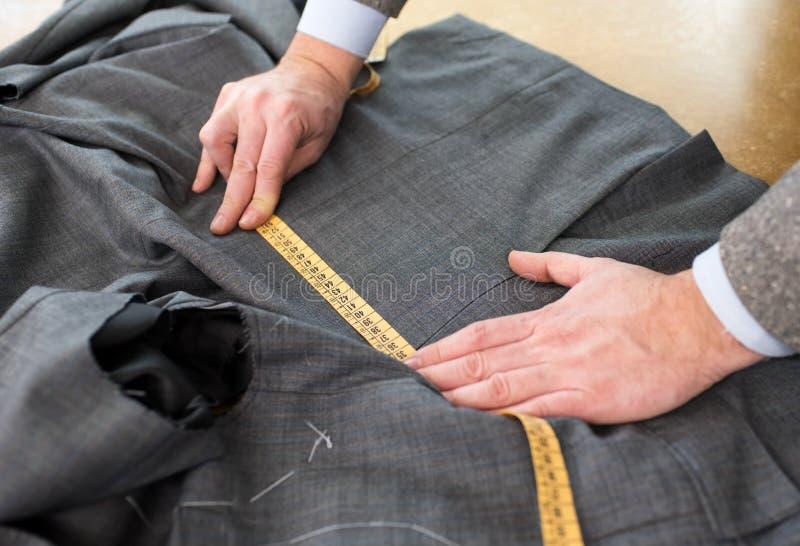 Закройте вверх по взгляду куртки портноя измеряя стоковые фото