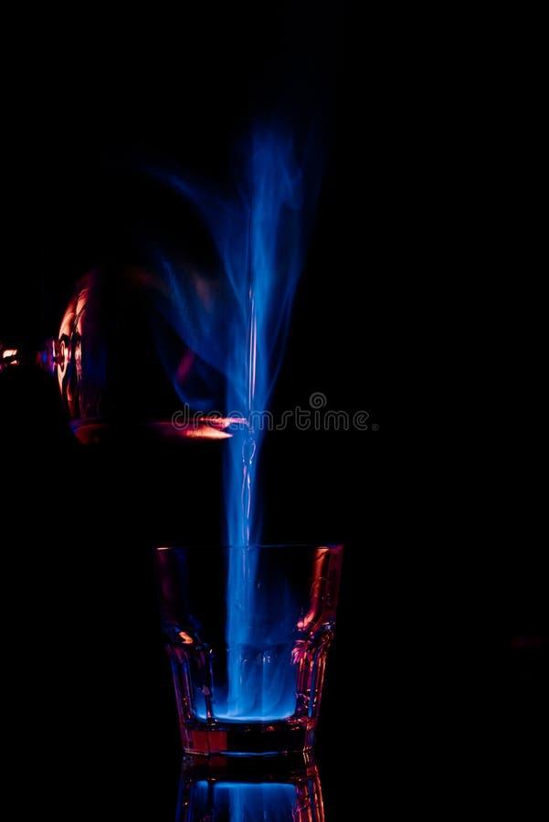 закройте вверх по взгляду лить горящего питья спирта sambuca в стеклянный процесс стоковое фото rf