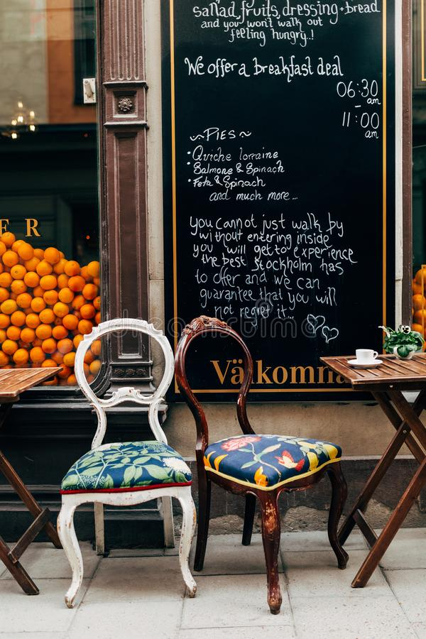 закройте вверх по взгляду меню, пустых стульев и чашки кофе на таблице кафа на улице стоковая фотография rf