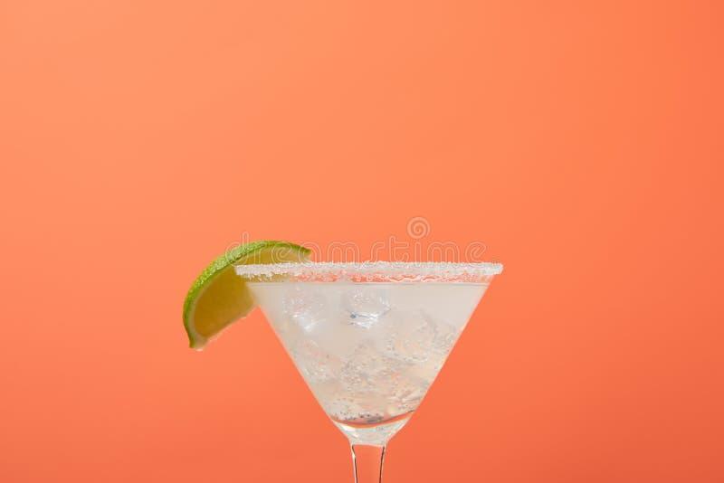 закройте вверх по взгляду освежая коктеиля маргариты спирта при известка и лед изолированные на апельсине стоковая фотография rf